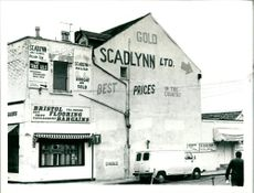 A photograph of building and a van.