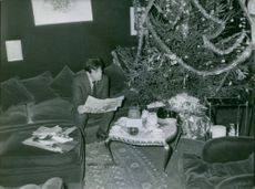 Théo Sarapo reading a newspaper beside the Christmas tree. 1964.