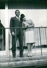 A couple standing on a balcony.