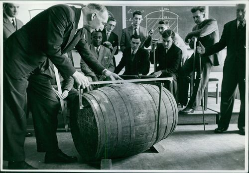 A group of men watch as an older man measures a barrel in front of them.