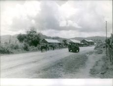 A vehicle loaded with soldiers passing by the road.