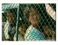 Vietnamese boat people wait behind barbed wire.