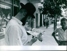 Man standing and reading newspaper and a child looking to him.