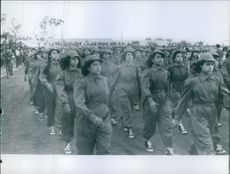 A large number of women in uniform marched together in the street.