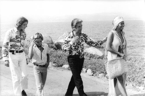 Claudia Cardinale walking on sea side with people.