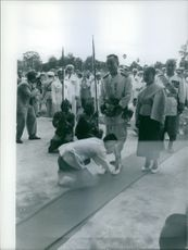 Man touching another man's feet and welcoming him during an event.