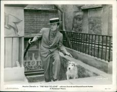 """Maurice Chevalier acting for the film """"The Way To Love"""" with a dog."""