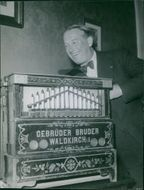 Maurice Auguste Chevalier standing with a board.