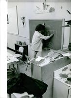 child standing on chair and making drawing on black board.1963