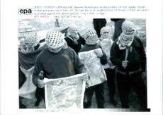 Masked palestinians holding posters.
