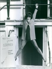 A gay model hanging his arms on a bar, outside a jewelry store.