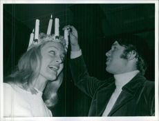 Kerstin Asp smiling as man lights the candles of her Lucia crown, 1968.