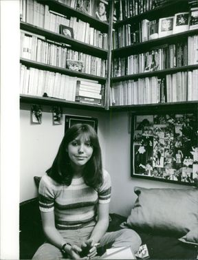 Woman sitting on bed, bookshelf in background.