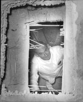 Hovjuveler Wiwen Nilsson looks up through the hole in the roof that the thieves used for the burglary.