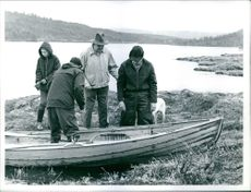 Norwegian politician Trygve Lie preparing to embark on a small boat on a lake.