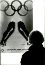 A poster for the 1972 Olympic Games is considered by unknown woman