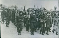 Captured German and Italian soldiers, including pilots, are marched along the docks at Algeria, North Africa, before being transported by ship to prison camps, 1943.