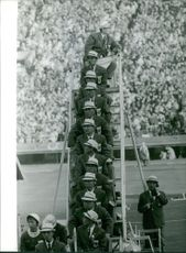 Japanese men wearing the same uniform sitting on a ladder.