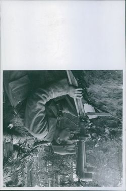 Soldier using fire extinguisher in forest and looking through the binocular.