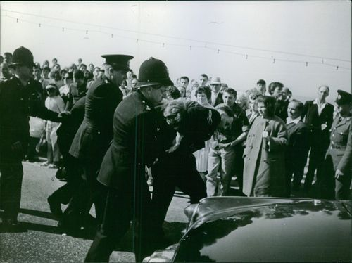 Policemen holding and taking away a prisoner and crowd looking.  1964 English greasers