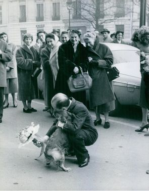Photograph of Jean Desses with a dog in street, people standing behind looking and smiling.