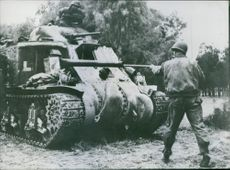 An American soldier cleans the cannon of a General Lee tank.