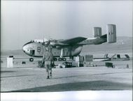 Man walking towards plane with cargo on the ground, Middle East.