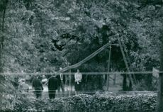 """People standing in a garden during the abduction of Eric Peugeot.  """"Reconstruction of the Peugeot abduction""""  1960"""
