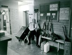 Man siting and inspecting the weapons.