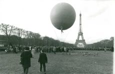 People gathered around  Eiffel tower with hot air balloon. February 1, 1971