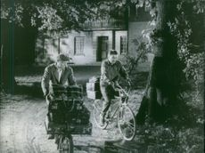 Men carrying luggage by bicycles at night.