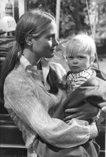 Leigh Taylor-Young carrying a small child.
