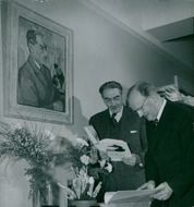 Professors Nils Odhner and John Runnström under a portrait of Odhner at the National Museum