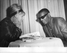 Ray Charles Robinson talking with a woman.