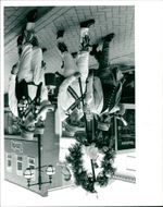 The King's Morris dancers dressed in their costume aloft the Garl flowers surrounding a doll.
