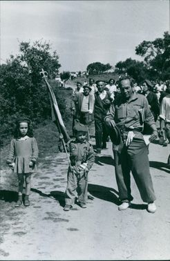 People walking down hill, child holding a flag.