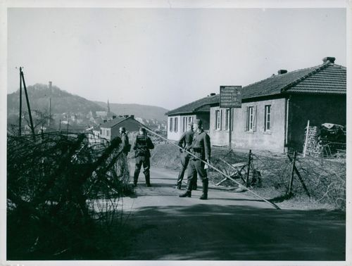 Soldiers standing in street and holding a pole during Tyskland War, 1940.