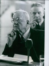 John Foster Dulles, leaning on a table with a pen on hand, attentively listening.