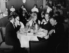 Pascale Petit sitting at table with Giani Esposito and Kirk Douglas.