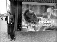 "A young man stands and smokes at an advertising poster for the beer ""Pilsekrone"""