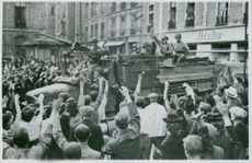 Crowd cheering for the army while on the parade.