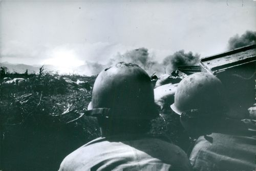 Soldiers in position looking at the explosion from afar, during the war in Vietnam, 1968.