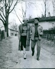 Daniel Gelin walking with woman.