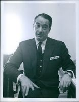 A photo of  Danish comedian, conductor, and pianist  Victor Borge sitting and in a conversation.