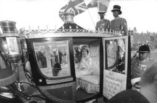 Elizabeth II sitting in her royal horse cart.
