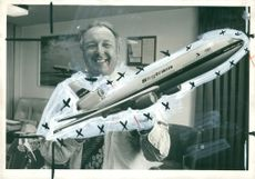 A man holding a miniature plane of Laker.