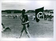 Man holding a flag and walking on the ground.