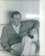 Roger Miller enjoying drink and relaxing on couch.