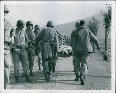 Marines moving up to the battle line pass a wounded man on a stretcher as he is carried back to a clearing station and give him a glance of sympathy, 1950.