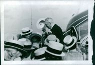 Maurice Auguste Chevalier standing among people, holding hat.